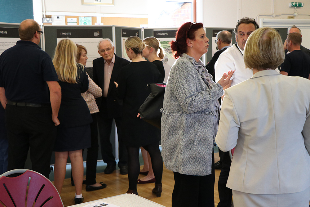 A public consultation room filled with a crowd of people